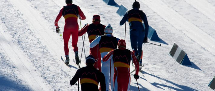 A group of men head to the finish line in a cross country ski race.